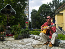 Man Plays Guitar On The Street. Adult man is playing jazz guitar on the street Royalty Free Stock Images