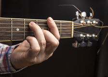 Man plays guitar, thumbs rearrange chords. Stock Photography