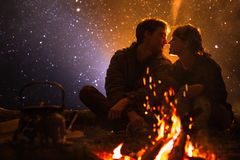Man plays guitar and woman about the fire on the background of the starry sky Royalty Free Stock Images