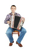 Man plays harmonica sitting on a chair Stock Photography