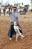 Man plays with his dog on the beach Stock Photos
