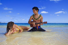 Man plays his ukulele for a young woman Stock Photo