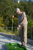 Man plays minigolf Stock Images