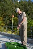 Man plays minigolf Stock Images