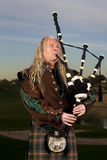 Man Plays Scottish Bagpipes at Dusk Stock Photo