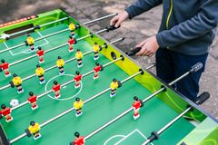 A man plays table football. Board game on the street. Recreation and entertainment in the summer on the street for young people royalty free stock photography