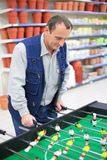 Man plays into  table football in store Stock Photo
