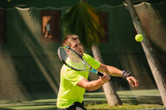 Man plays tennis in bright cloth Royalty Free Stock Photo