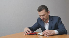 The man plays with toy cars stock footage