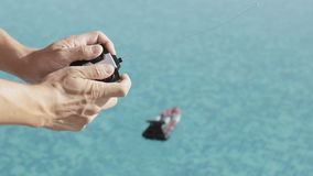 A man plays with a toy boat. A man plays with a toy ship. the adult is engaged in children`s affairs. radio controlled motor boat swims in the pool stock video
