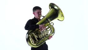 Man plays on the tuba melody. White studio, slow motion stock video footage