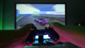 A man plays a video game at home by the TV. In the hands of holding a gamepad. Plays a racing simulator.  stock video footage