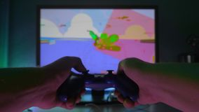 A man plays a video game at home by the TV. In the hands of holding a gamepad. Plays a racing simulator.  stock footage
