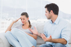 Man pleading with his upset partner on the couch Stock Photos