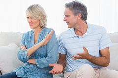 Man pleading with his wife after a fight. At home on the couch royalty free stock images