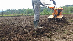 Man plowing field with cultivator, garden preparation stock video footage