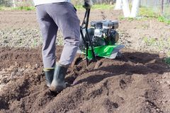 A man plowing the land with a motor-block, preparing the land for planting potatoes.  Royalty Free Stock Photo