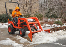 Man plowing snow and ice. From driveway stock images