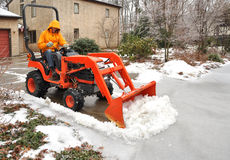 Man plowing snow and ice. From driveway royalty free stock images