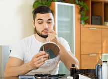 Man plucking hair from his nose with pliers Royalty Free Stock Photo