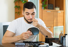 Man plucking hair from his nose with pliers Stock Photos