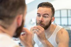 Man plucking his nasal hairs Stock Photography
