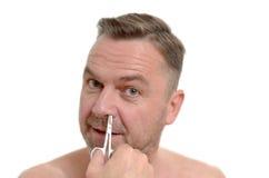 Man plucking his nose hairs with tweezers Stock Image