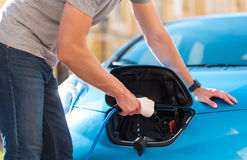 Man plugging cable in hybrid car Royalty Free Stock Photography