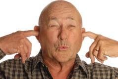 Man plugging ears. Bald senior man plugging ears with fingers Royalty Free Stock Image