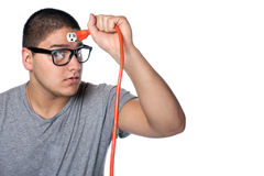 Man Plugging Himself In. Conceptual image of a young man holding an electrical chord disconnected from the outlet on his forehead stock photo