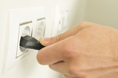 Man plugging in or unplugging an electrical plug in a socket Stock Photography