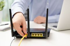 Man plugs Ethernet cable into router Royalty Free Stock Photos