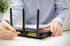 Man plugs Ethernet cable into router Stock Photos
