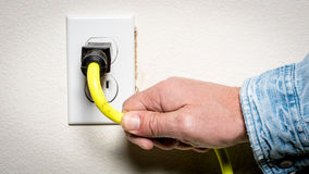 Man plugs an extention cord into a garage outlet Royalty Free Stock Image