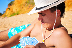 Man plying cards on the beach Stock Photography