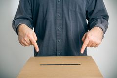 Man Pointing At Ballot Box. Inviting you to cast your vote Royalty Free Stock Image