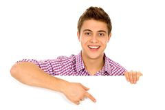 Man pointing at a blank board. Young man holding blank poster Royalty Free Stock Images