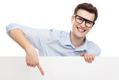 Man pointing at blank poster. Young man with blank whiteboard Stock Image