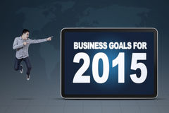 Man pointing at business goals for 2015. Success man jumping while pointing at a board of business goals for 2015 vector illustration