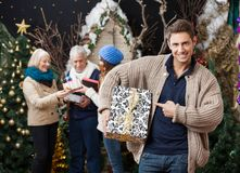 Man Pointing At Christmas Present With Family In Stock Photo
