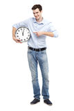Man pointing at a clock. Young man over white background Royalty Free Stock Photo