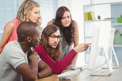 Man pointing at computer while working with coworkers Stock Image