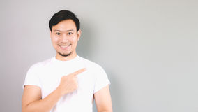 A man pointing on the copyspace, empty content. An asian man with white t-shirt and grey background stock photos