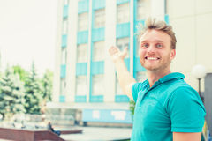 Man pointing in direction of apartment. New apartment in tall building stock image