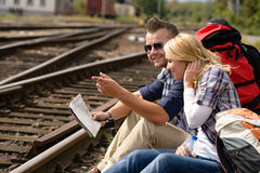 Man pointing direction with map on railroad Stock Photo