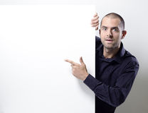 Man pointing at an empty billboard on white Royalty Free Stock Photos