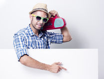 Man pointing at an empty billboard on white. Young man with pointing finger at an empty billboard saying put your own text here, wearing glasses and holding old Stock Photo