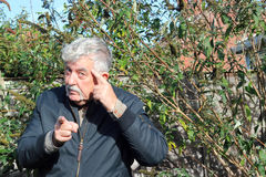 Man pointing finger and doing think gesture. An elderly man looking and pointing towards the camera. The man is also touching his head as a gesture to tell the royalty free stock photo