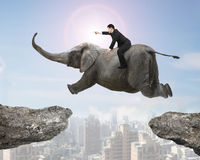 Man with pointing finger riding elephant flying over two cliffs Stock Photo