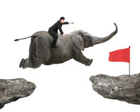 Man with pointing finger riding elephant flying toward red flag Royalty Free Stock Photography